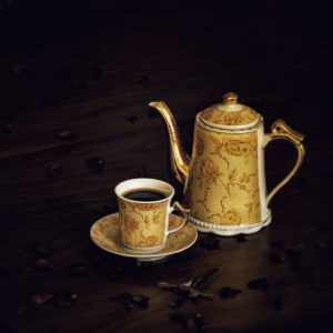 white and brown ceramic teapot beside white ceramic mug on brown wooden table