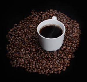 white ceramic mug on coffee beans